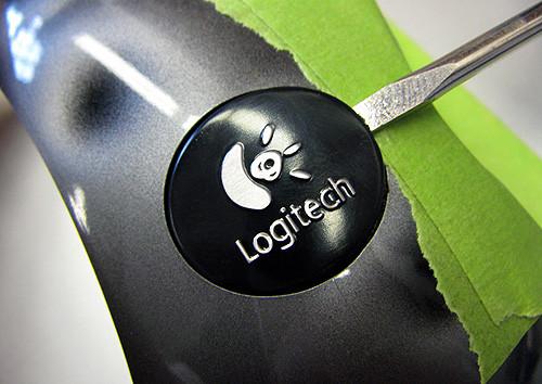 Поддеваем логотип Logitech с помощью небольшой плоской отвертки. Малярный скотч защищает поверхность от повреждения отверткой